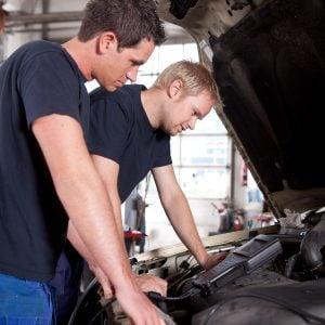 Two man mechanics looking a diagnostics equipment, servicing car